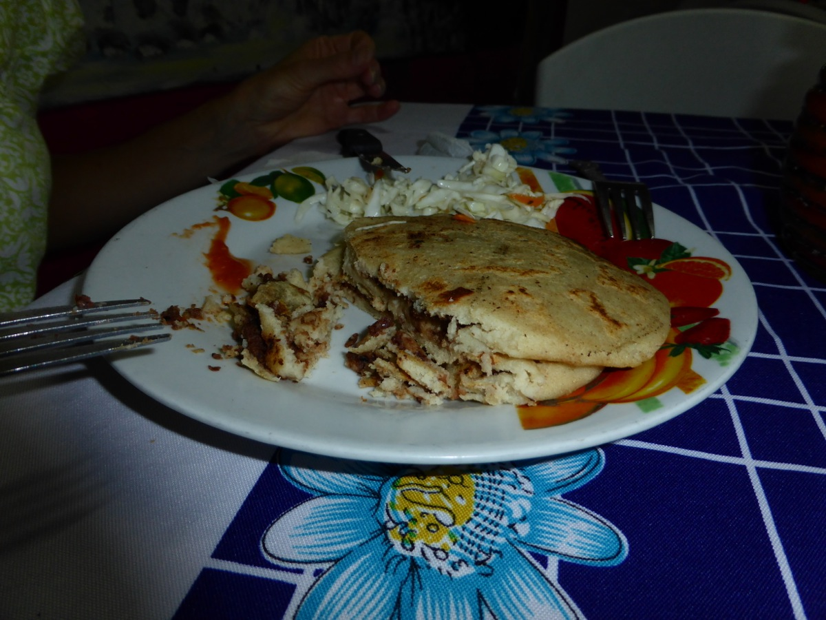 Pupusas stuffed with beans and topped with pickled cabbage and hot sauce